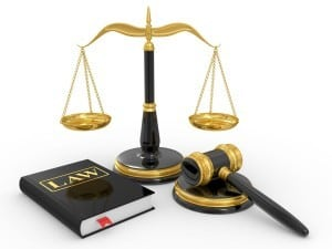 Scales, a gavel and a law book on a white background