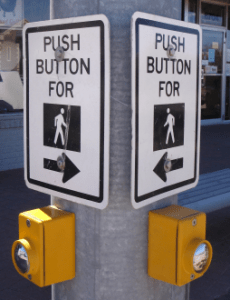 Cross walk buttons for pedestrians at a street corner