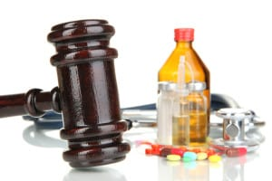 A gavel, stethoscope and perscription drugs on a white table