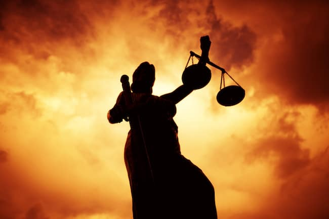 Blind Themis, sword in hand holding balanced scales represents justice