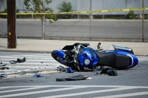 A wrecked motorcycle surrounded by debris lies in the middle of an intersection