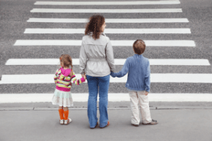 A mother teaches her children how to safely cross a busy street