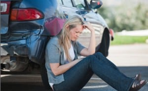 An upset woman sits with her back against her car holding her head after an accident
