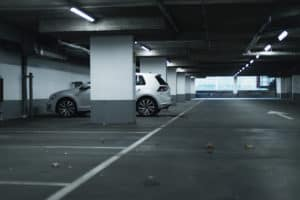 White car parked in empty parking garage.