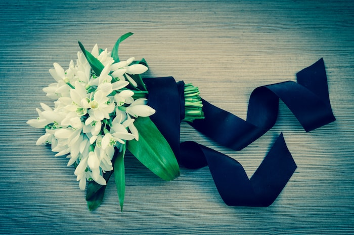 bunch of white snowdrops over wooden background funeral concept