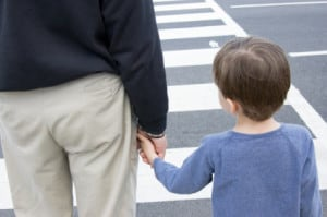 A father teaches his son how to safely cross a busy street