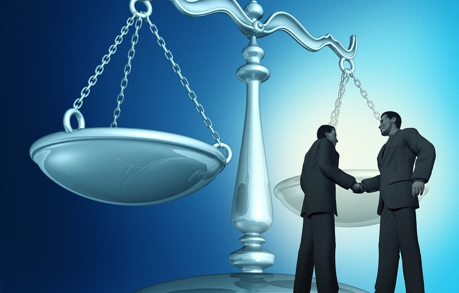 A proud lawyer and thankful client shake hands with the scales of justice in the background