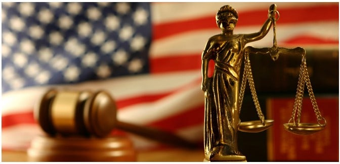 Blind Justice statue with a Gavel displayed with an American Flag in the background