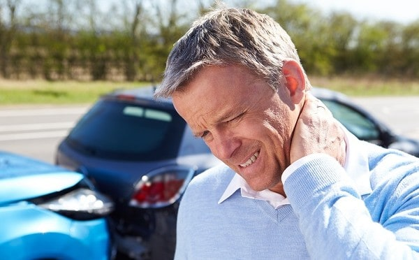 A man holds his neck after suffering whiplash in an auto accident