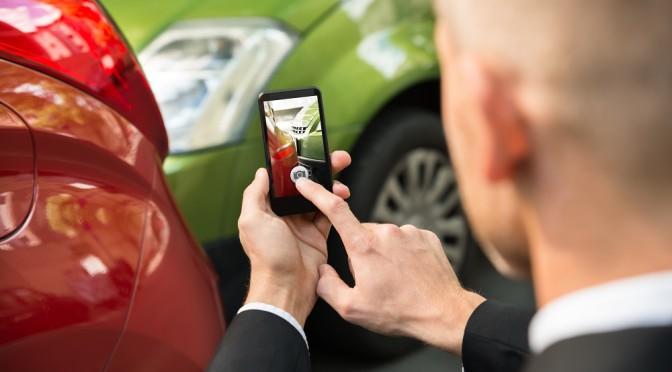 man photographing car wreck