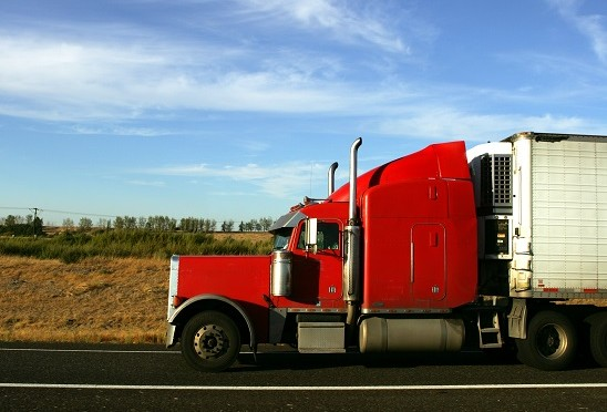A Red 18 wheeler cruises on down the highway