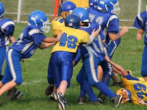 Pee-Wee Football players run a play during a game