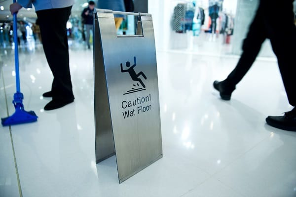 A janitor mops a floor as a wet floor caution sign warns visitors