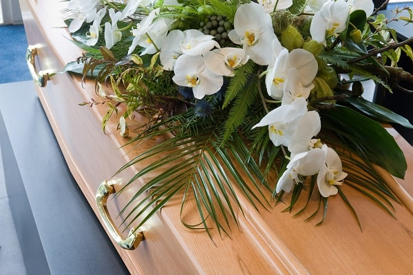 A flower arrangement tops a coffin at a wake