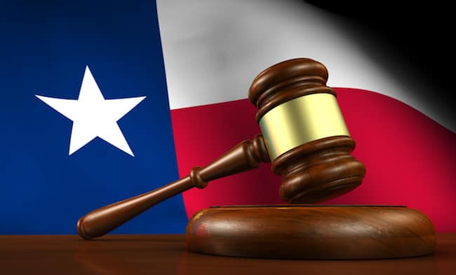 A 3d render of a gavel on a wooden desktop and the Texas flag on background.