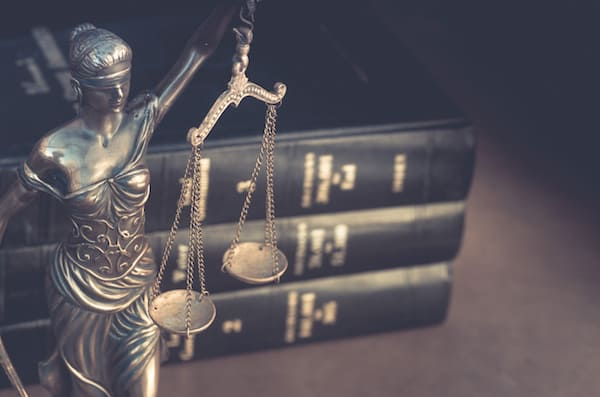 Justitia, Blindfolded and holding balanced scales near a stack of law books