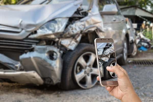 After an Accident, a driver documents damage with a smartphone