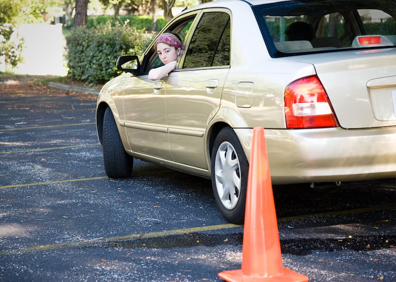 A teenager practices backing a car up using traffic cones as a guide