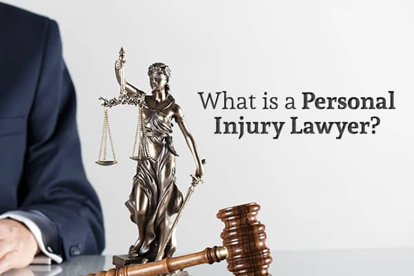 "A man sits at a table beside a Lady Justice statue, a gavel, and the words ""What is a Personal Injury Lawyer?"""