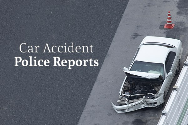 "A wrecked white car on the shoulder of a highway beside the words ""Car Accident Police Reports"""